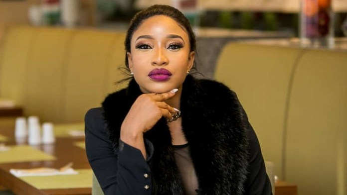 Tonto Dikeh wearing black with her right arm under her chin
