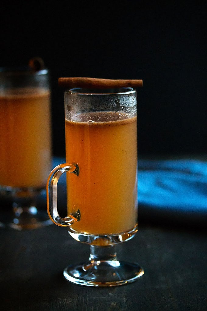 a mug of apple cider hot buttered rum with a stick of cinnamon on top