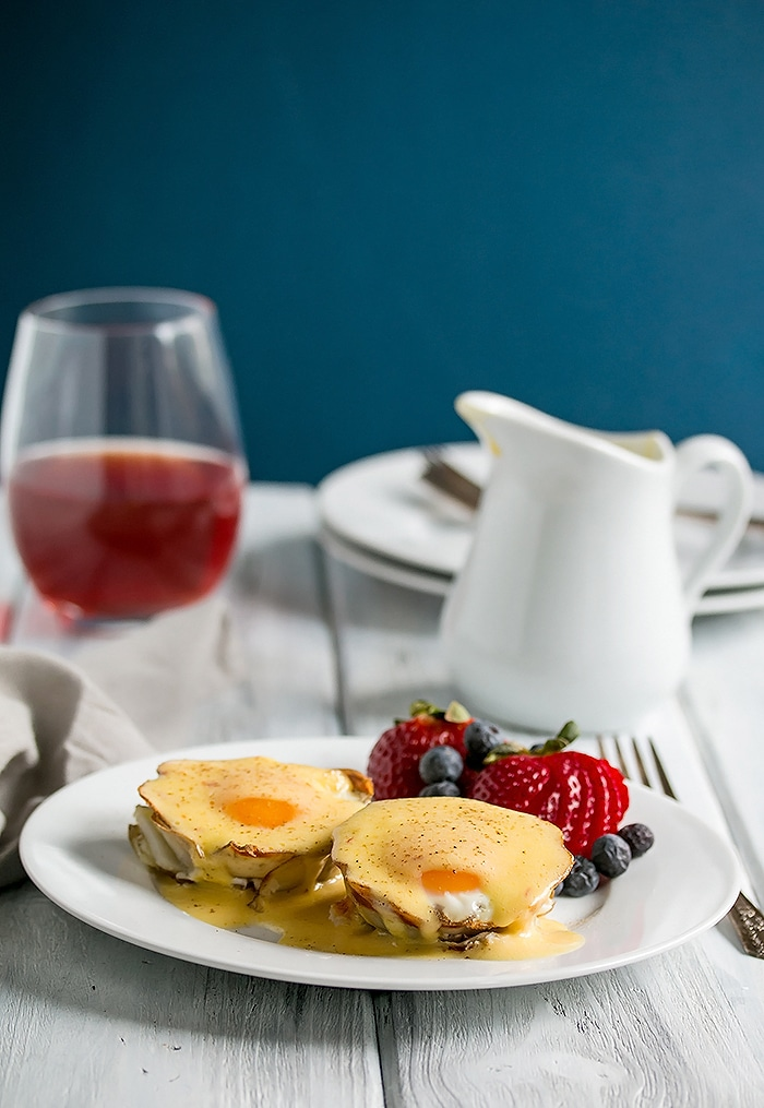 eggs benedict on a plate and drenched with hollandaise sauce