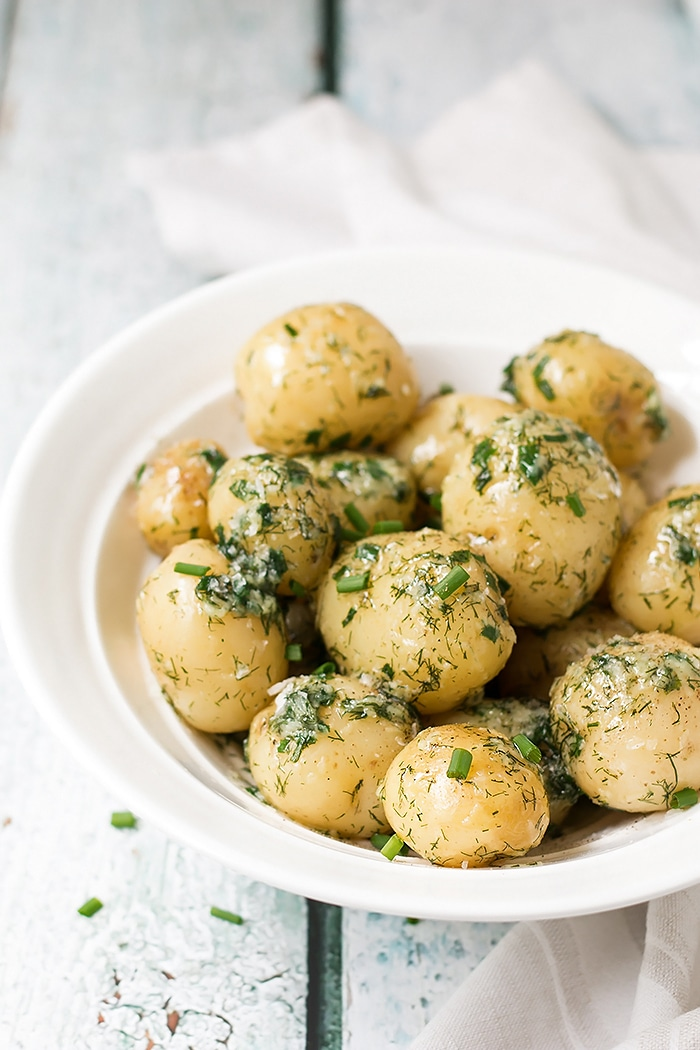 potato side dish with garlic and dill in a white serving bowl