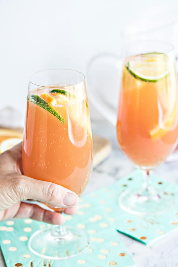 a hand grabbing a glass of planters punch