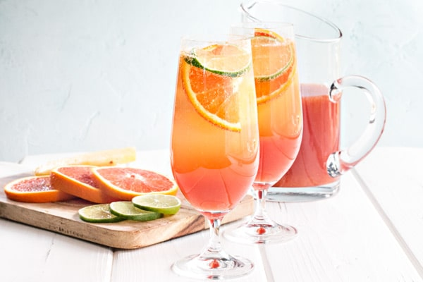 two glasses of rum punch with a pitcher and some slices of orange and lime