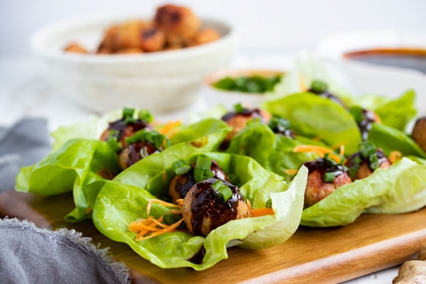 a tray of meatballs in lettuce wraps drizzled in gyoza sauce