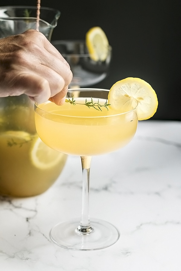 a lemon cocktail in a coupe glass with a hand placing a piece of thyme  on top