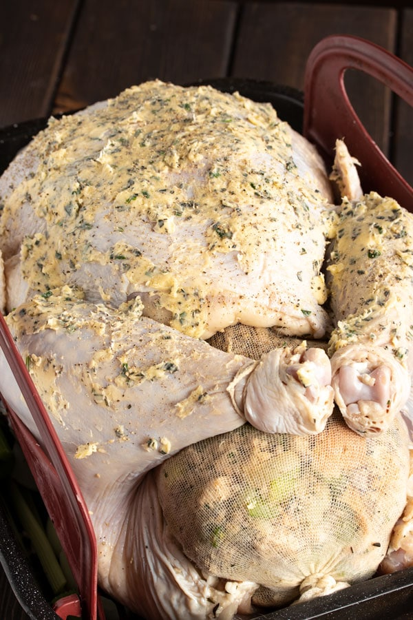a brined and stuffed turkey in a roaster pan with butter and rosemary rubbed on the skin
