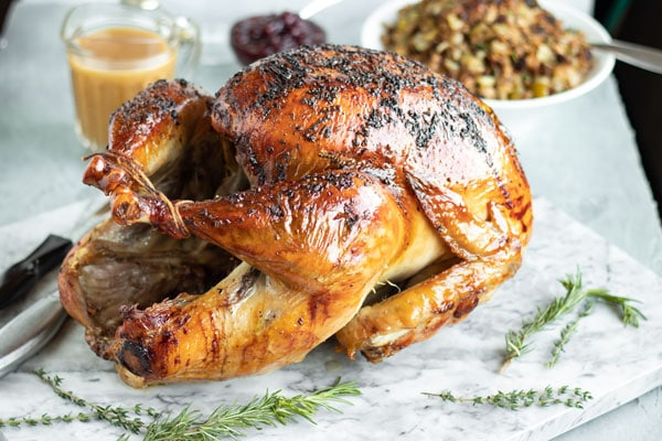 A side view of a turkey with stuffing, gravy, and cranberry sauce in the back ground