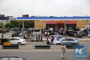 People queue with their vehicles to buy fuel in front of a fuel station at Agege district in Lagos, Nigeria April 5, 2016