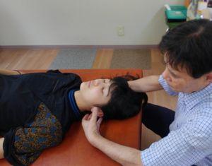 女性の患者に施術をする院長の写真