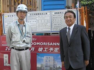 大森山王マンション現場看板前にて 左から松本所長、中山社長