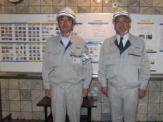 左から釜山現場代理人、中山社長 ※後ろの掲示板に全作業員の顔写真を掲載