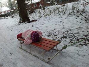 Kind auf einem Schlitten im Schnee