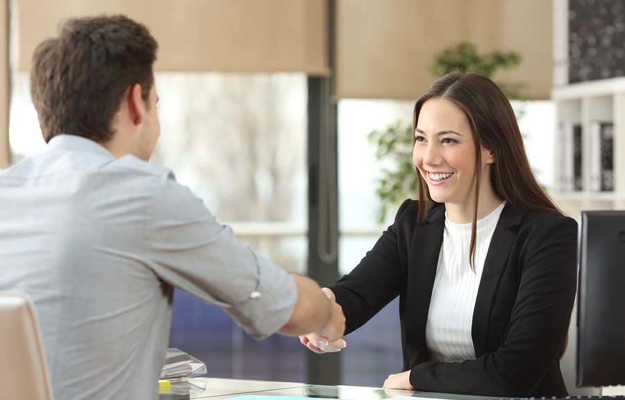 man and woman shaking hand in office