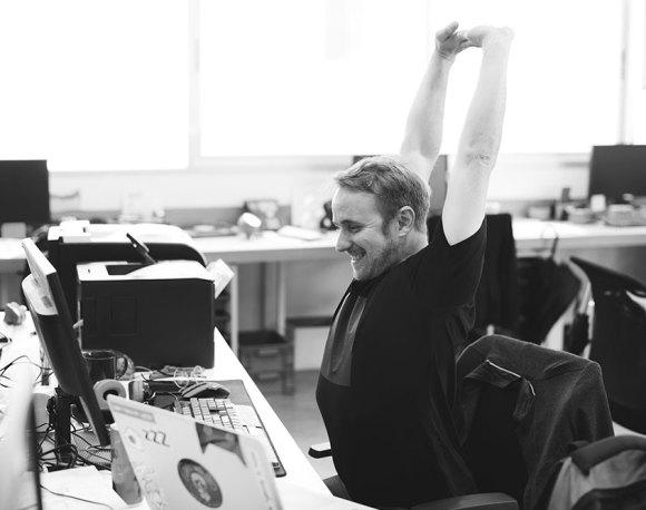 man stretching at his desk