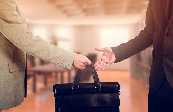 hands transferring briefcase