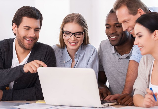 group of people looking at laptop