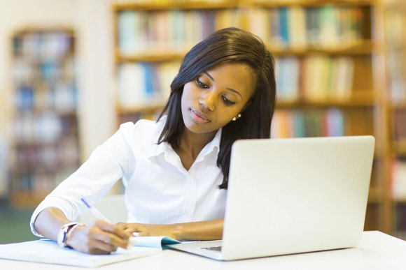 young woman writing with laptop