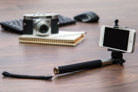 smartphone, selfie stick, camera, and notebook