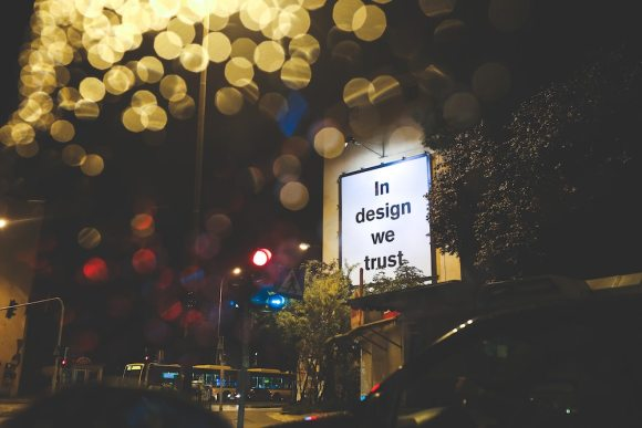 "sign on street saying ""in design we trust"""