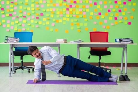 man doing sideways pushup in office