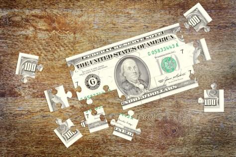 $100 bill cut into puzzle pieces