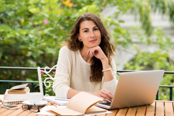 woman at laptop with notebook