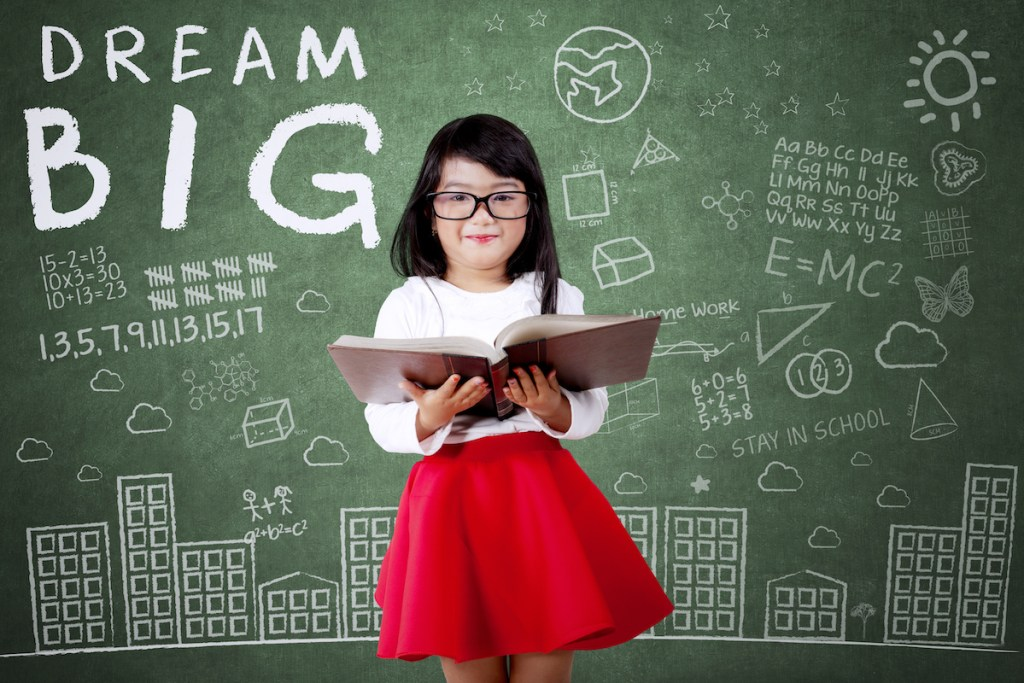 girl with book in front of blackboard with dream big and science designs