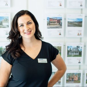 Real Estate Agent in Front of Paper Listings