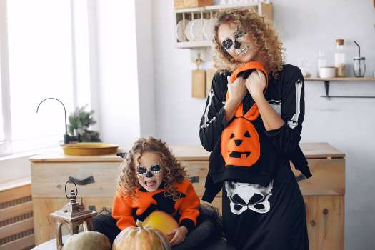 Halloween. Mother and daughter in halloween costumes. Family at home with pumpkins.