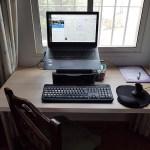 Laptop on a desk in fron of a window