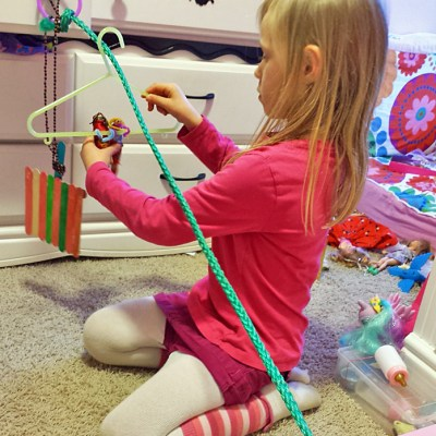 After realizing she could not build a full-sized zip line in our yard with this piece of rope, my daughter made a small one for the dolls.  zip line dolls