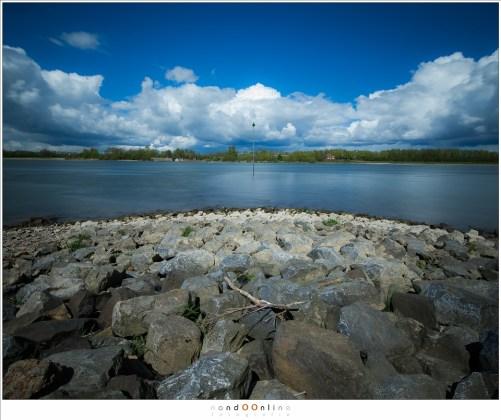 Een stilstaand moment, waarin de rivier de Waal voorbij stroomt en de wolken aan de horizon langzaam maar zeker onderweg zijn.