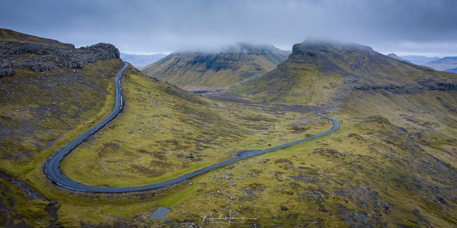 De weg Oyggjarvegur die van de doorgaande weg naar een prachtig fjord leidt.
