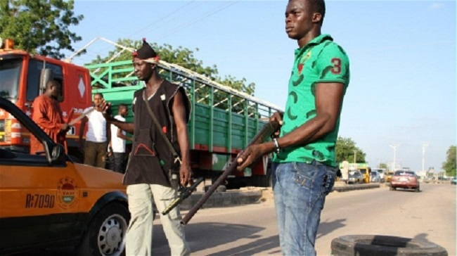 Civilians mount a roadblock in the northeastern city of Maiduguri, searching for Boko Haram suspects