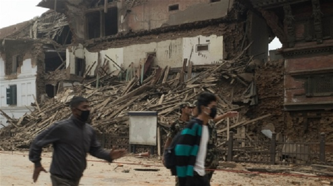 Men run past a collapsed building in Basantapur in central Kathmandu during an aftershock