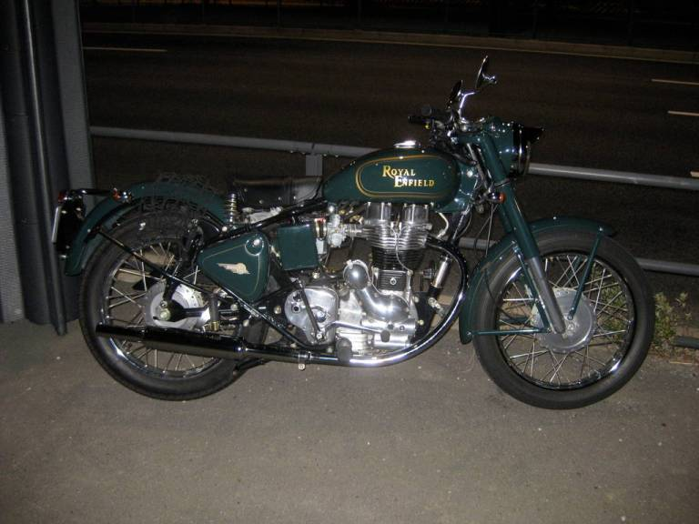 A royal enfield 350 just parked up by the side of the road in the middle of the night.