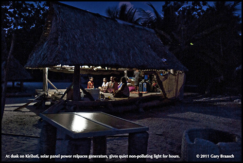 The family of Bepano Tamara in Nooto village, North Tarawa, is enjoying increased nighttime use of their thatch-roofed home with the small solar panel set seen in the foreground.  The panel charges a car battery during the day and the battery runs a single CFL bulb for most of the night, so the family and friends can read, study and weave mats. This eliminates the need for a generator and the cost of kerosene of up to $70 a month -- and its noise, odor and pollution.