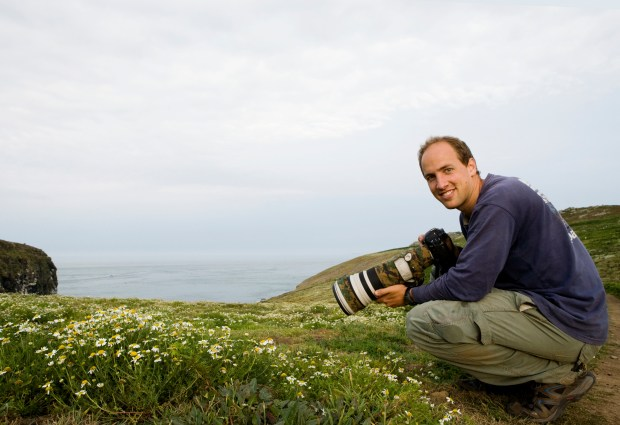 Sebastian Kennerknecht photographing on coast, Skomer Island National Nature Reserve, Skomer Island, Pembrokeshire, Wales, United Kingdom