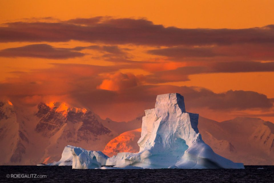 Photo of sunset behind a large iceberg. © Roie Galitz.