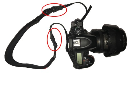 photo of a camera with strap that has quick release attachments. Failing to properly fasten these connections can lead to a dropped camera.