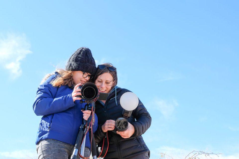 Two young photographers looking at camera in field