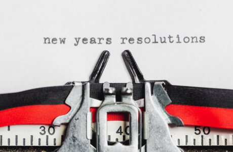 The words 'new years resolutions' are displayed in the center of a page on a vintage typewriter.