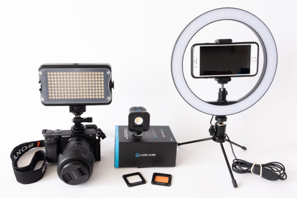 A few of the many options for lighting yourself in a Zoom meeting:  (left to right) an LED panel  with a diffusion filter on the hot shoe of a camera, a Lume Cube with filters, and a ring light with an attachment for a smart phone.