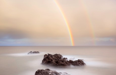 """A long exposure seascape with a double rainblow brilliantly glowing above. Showcase 2021: """"Kiss on the Horizon, Maui, Hawaii,"""" Best in Category, Scapes © Scott Reither"""