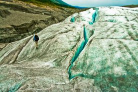 Solitary hiker on Root Glacier in immense Wrangell-St. Elias National Park, Alaska