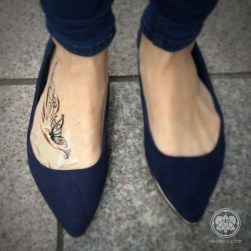 An un-healed tattoo of a butterfly and ornate decoration on the right foot.