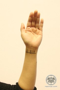 A small tattoo of an ECG scan on a woman's inner wrist.