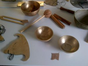 This image shows a table display of bronze bowls, wooden sticks, a cloth covered gong stick, and a flat bronze gong in a shape that resembles a bell, a Tibetan Lama's hat, or a Buddha.