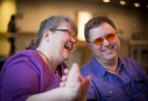 This image shows Riitta Lahtinen and Russ Palmer laughing and smiling, with their joined hands outstretched to the viewer.