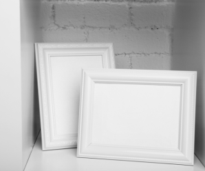 two white picture frames in a white shelf with a white wall background