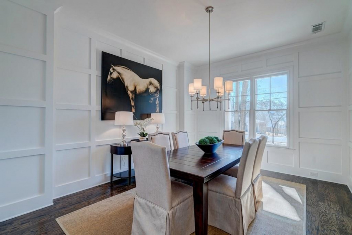 An all white dining room with a painting of a horse prominently displayed on one wall.